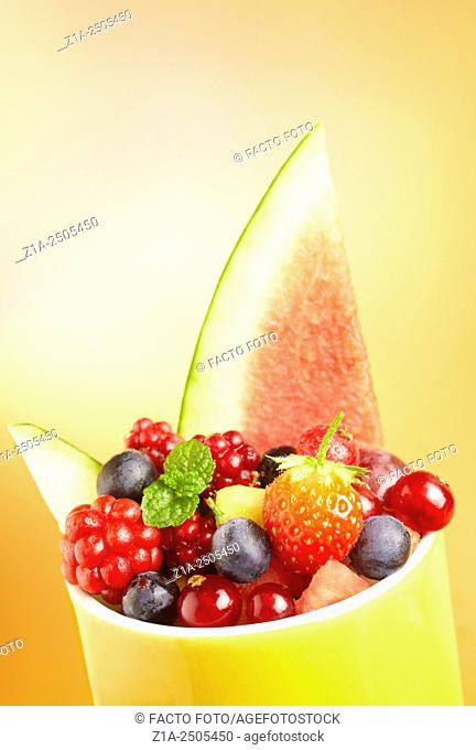 Yellow cup full of assorted berries and watermelon on an orange background