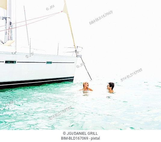Couple swimming near sailboat