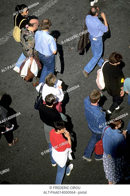 Group of people standing on asphalt, high angle view