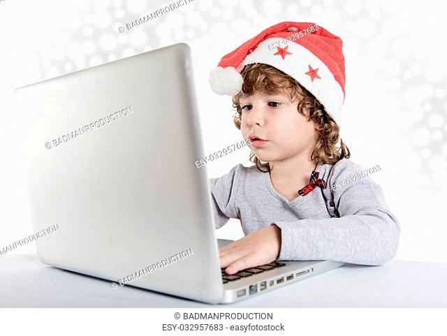 Little child writting letter to Santa Claus on laptop computer,selective focus