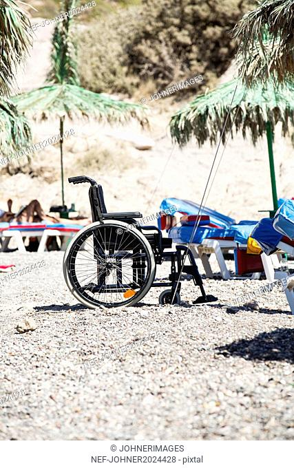 Wheelchair near sun chair on beach