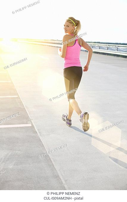 Young woman jogging, looking over shoulder