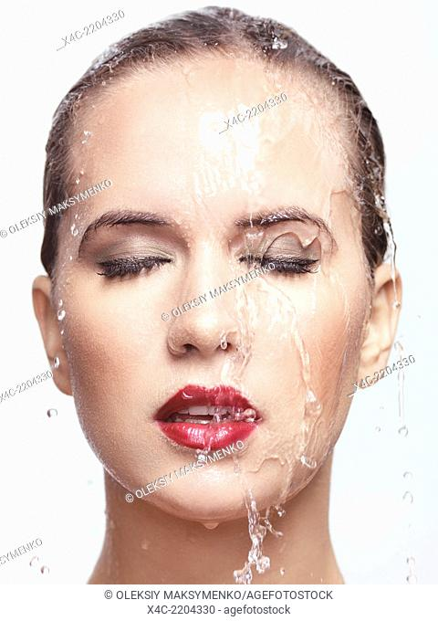 Closeup beauty portrait of a woman face with red lipstick and makeup with water running over it. Isolated on white background