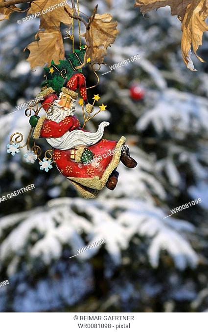 Saint Nicholas tree ornament hanging in a snow covered forest