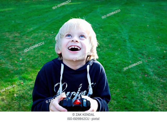 Boy holding remote control looking up smiling