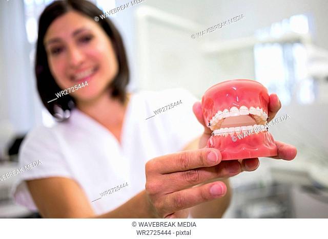 Portrait of female dentist holding a set of dentures