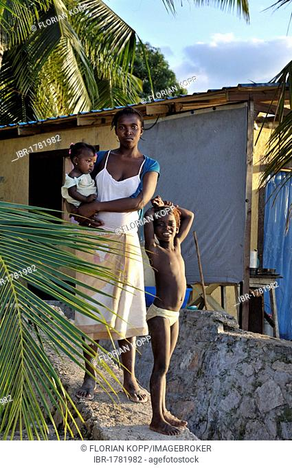 Mother with children standing in front of an earthquake-proof prefabricated house, provided to her by an aid organization, Petit Goave, Haiti, Caribbean