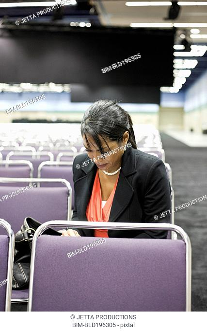 Black businesswoman waiting in empty conference center