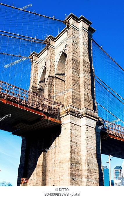 Low angle detail of Brooklyn Bridge and blue sky, New York, USA