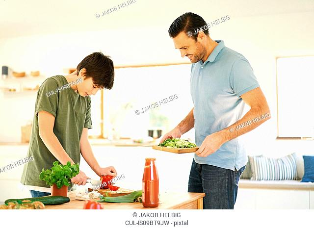 Boy slicing red pepper at kitchen counter, father watching