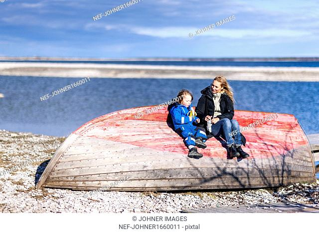 Mother and son sitting on boat on beach