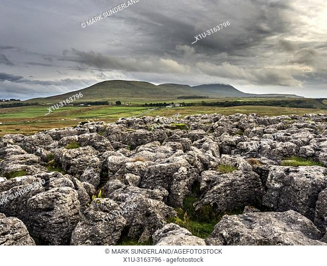 Dark clouds over Ingleborough from limestone pavement at Ribblehead Yorkshire Dales England