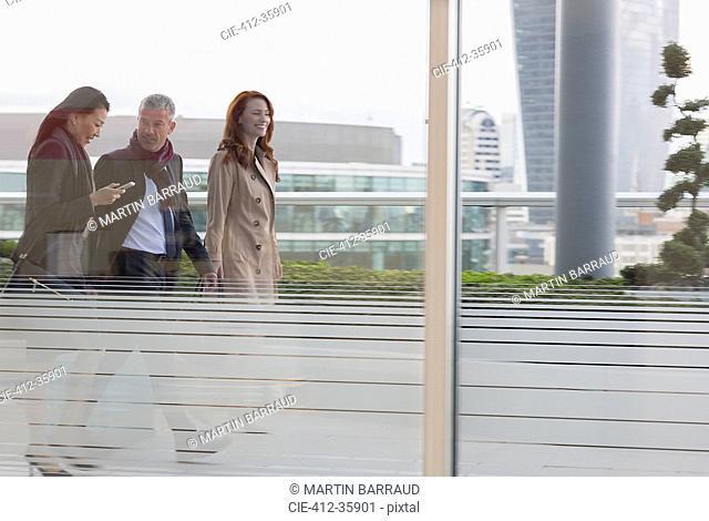 Business people walking on urban highrise balcony