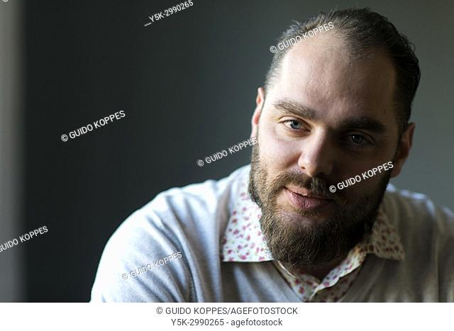 Tilburg, Netherlands. Studio portrait of a adult, caucasian male telling personal an intimate stories, with a blurry, gray background behind him