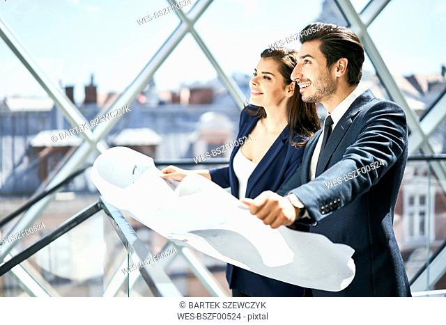 Smiling businesswoman and businessman holding plan in office