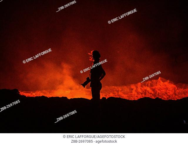 Ethiopia, Afar Region, Erta Ale, tourist in front of the living lava lake in the crater of erta ale volcano