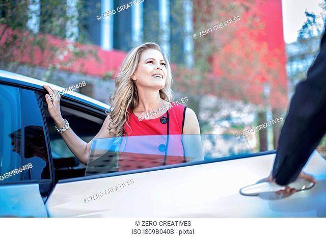 Man opening car door for city businesswoman