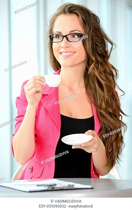 Business woman at work. Confident young business woman sitting at her working place and drinking coffee