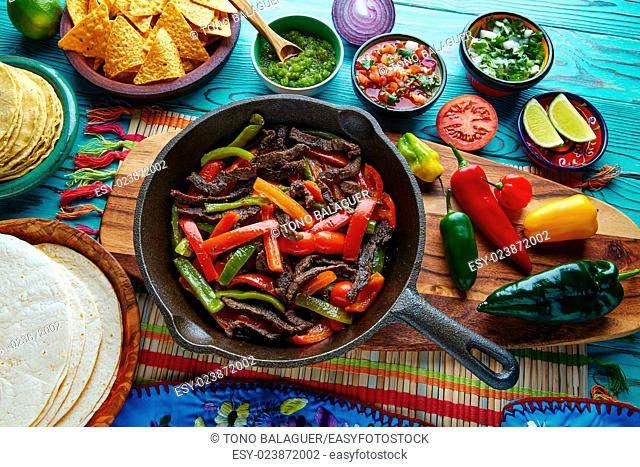 Beef fajitas in a pan with sauces chili and sides Mexican food