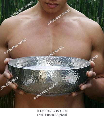 Man holding a metal bowl