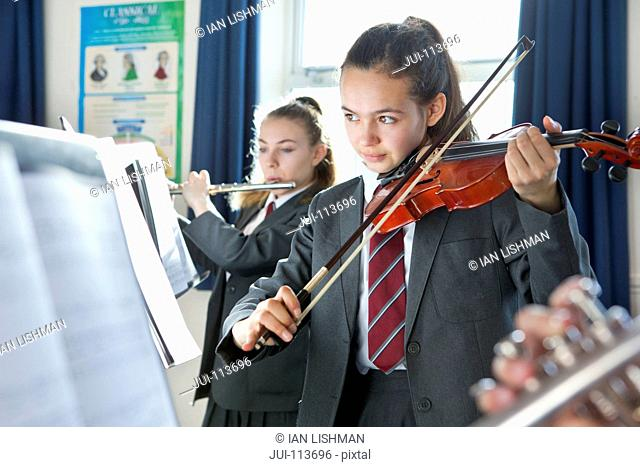 High school students playing violin and flute at music stands in music class