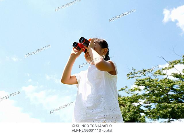 Japanese young girl with binoculars in a city park