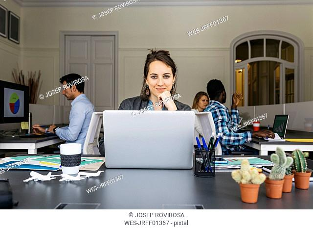 Young businesswoman using laptop, colleagues working in background