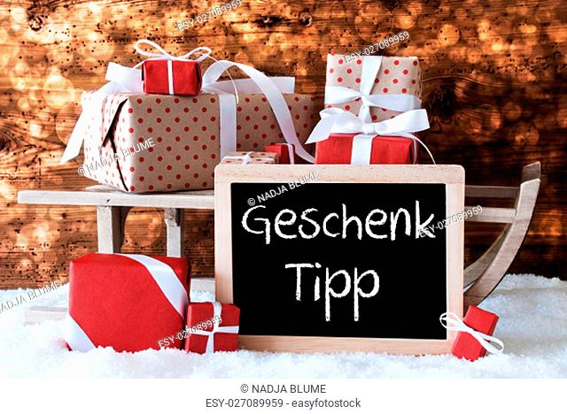 Chalkboard With German Text Geschenk Tipp Means Gift Tip. Sled With Christmas And Winter Decoration. Gifts And Presents On Snow With Wooden Background And Bokeh...