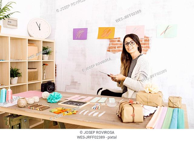 Young woman doing crafts at home, sitting at desk wth tablet