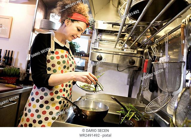 Female chef preparing food in frying pan