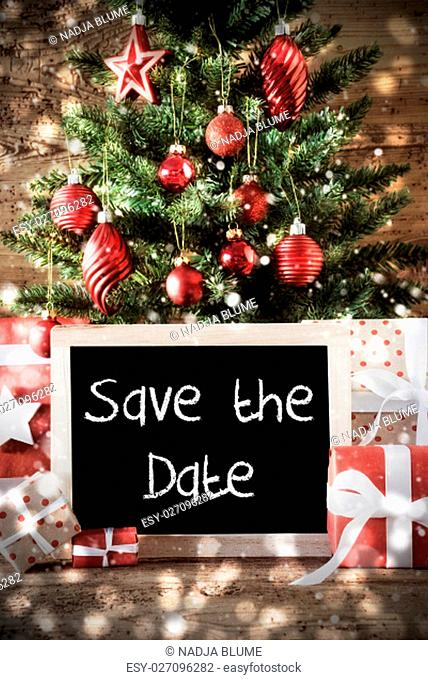 Chalkboard With English Text Save The Date. Christmas Card For Seasons Greetings. Christmas Tree With Balls. Gifts Or Presents In The Front Of Wooden Background
