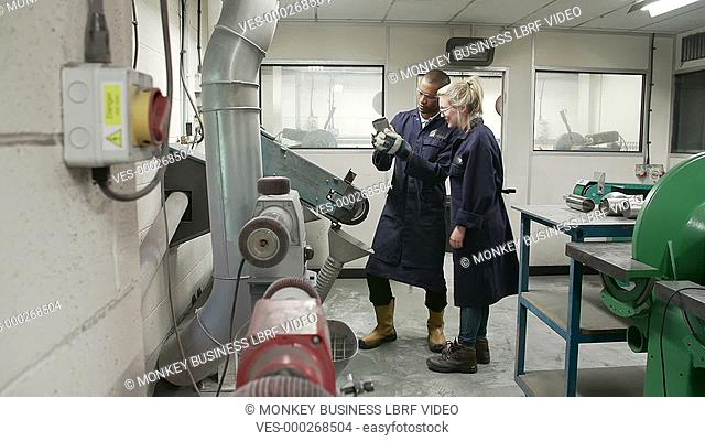Engineer explaining to female apprentice how to operate grinding machine as she asks questions.Shot on Sony FS700 in PAL format at a frame rate of 25fps