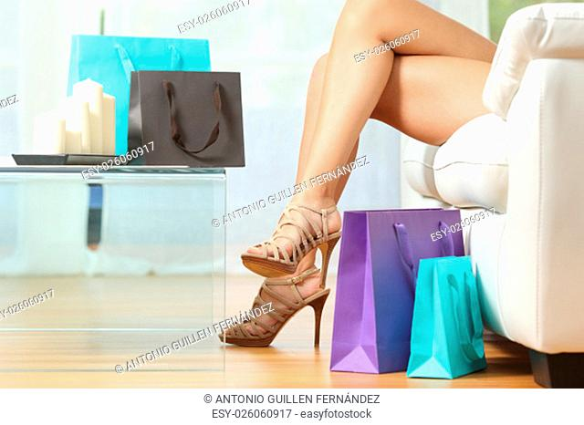 Fashion shopper legs with shopping bags sitting on a couch at home