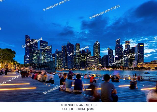 Tourists looking at city skyline from waterfront at dusk, Singapore, South East Asia
