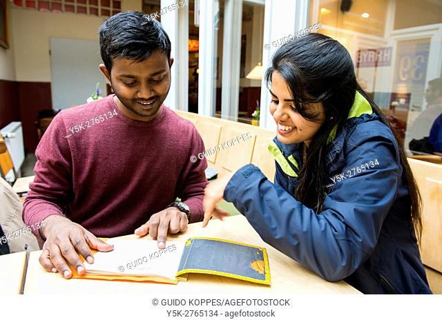 Aachen, Germany. Young Indian couple ordering a cup of tea, while visiting a down town cafe