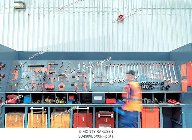 Locomotive engineer picking tools in train works
