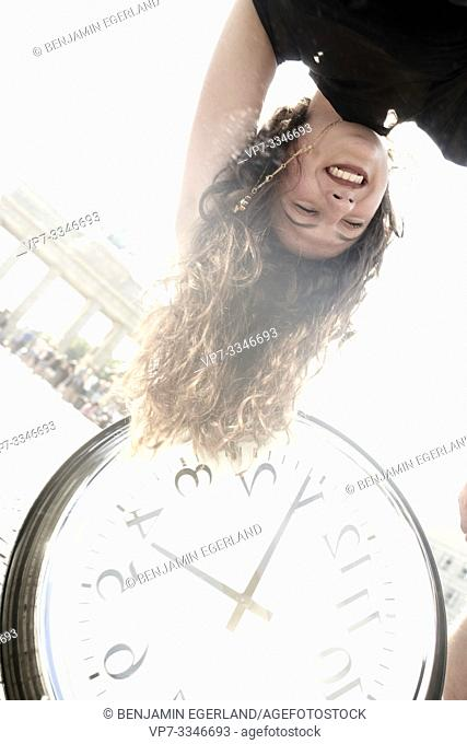 happy woman upside down with clock at street next to touristic sight Brandenburger Tor, Brandenburg gate, in Berlin, Germany