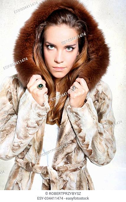 Beautiful long-haired model posing in a fur coat with unhappy expression