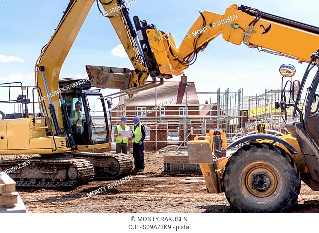Builders with machinery on housing building site