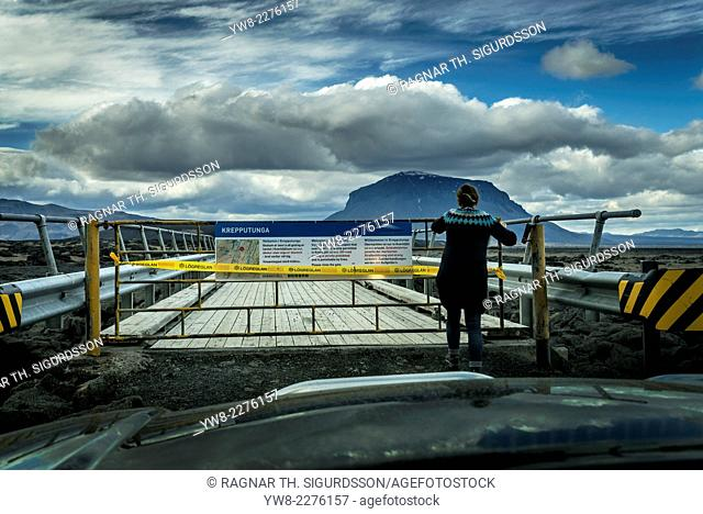 Woman standing by a closed bridge-Krepputunga area, by the Holuhraun Fissure Eruption, near the Bardarbunga Volcano, Iceland