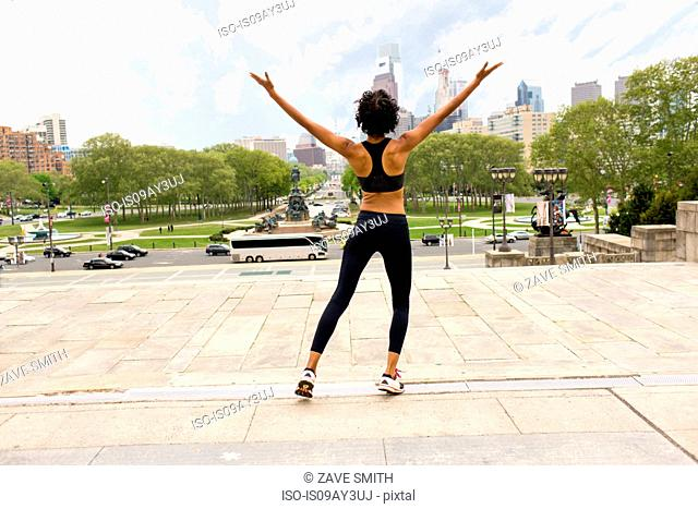 Rear view of woman wearing sports clothing, arms raised looking at city