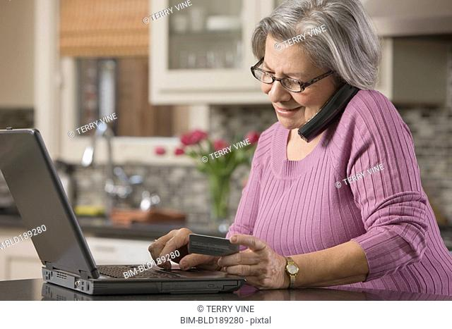 Senior Hispanic woman shopping online with credit card