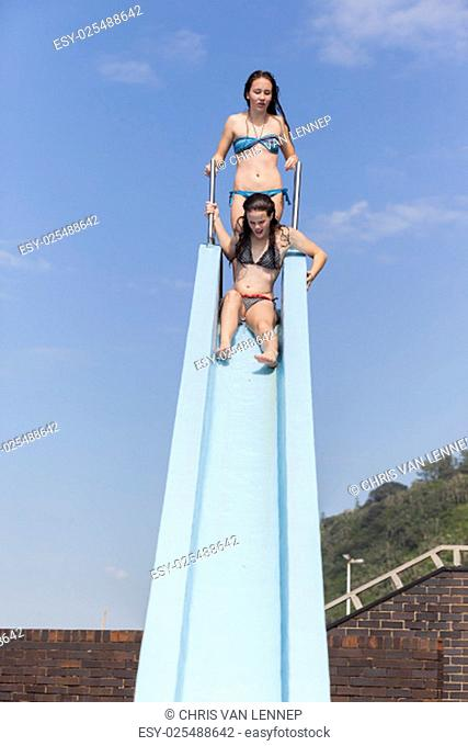 Girl teenager on swimming pool water slide summer fun