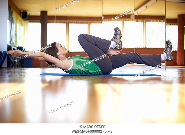 Woman in fitness studio doing abdominal trainiing