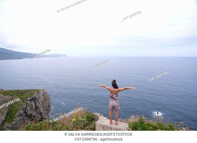 Woman enjoying the air of the cliffs of San Juan de Gaztelugatxe, Basque Country, Bermeo, Biscay, Spain, Europe