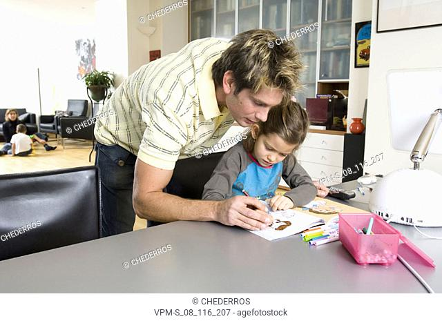 Father and his daughter coloring in a coloring book