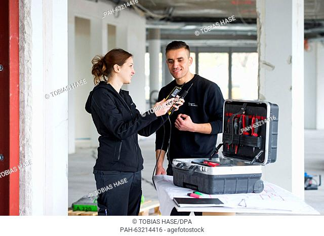 Trainee and future electronics technician Mati Bashir Samer (R) and his trainer, electronic technician master Alexander Schoener talk while Schoener holds a...