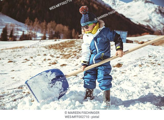 Italy, Val Venosta, Slingia, small boy using a large snow shovel