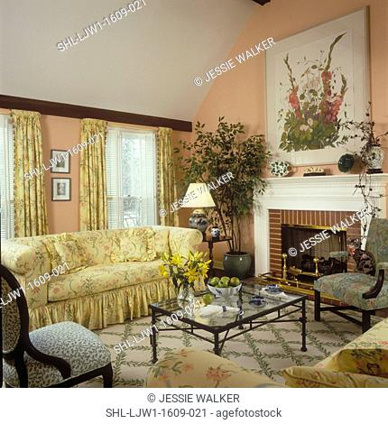 LIVING ROOM: Pale peach color walls, vaulted ceiling, yellow floral print sofa, matching pole pocket drapes, shutters, iron and glass coffee table, fireplace