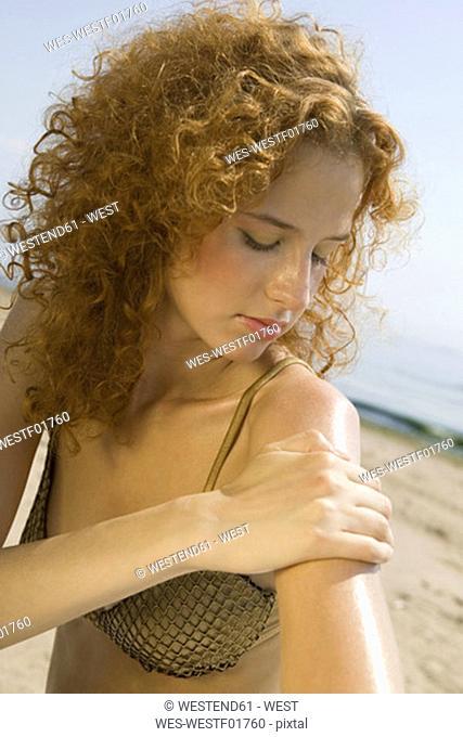 Young woman applying sun cream on beach, close-up